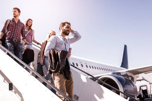 Group of young passengers disembarking the airplane. stock photo