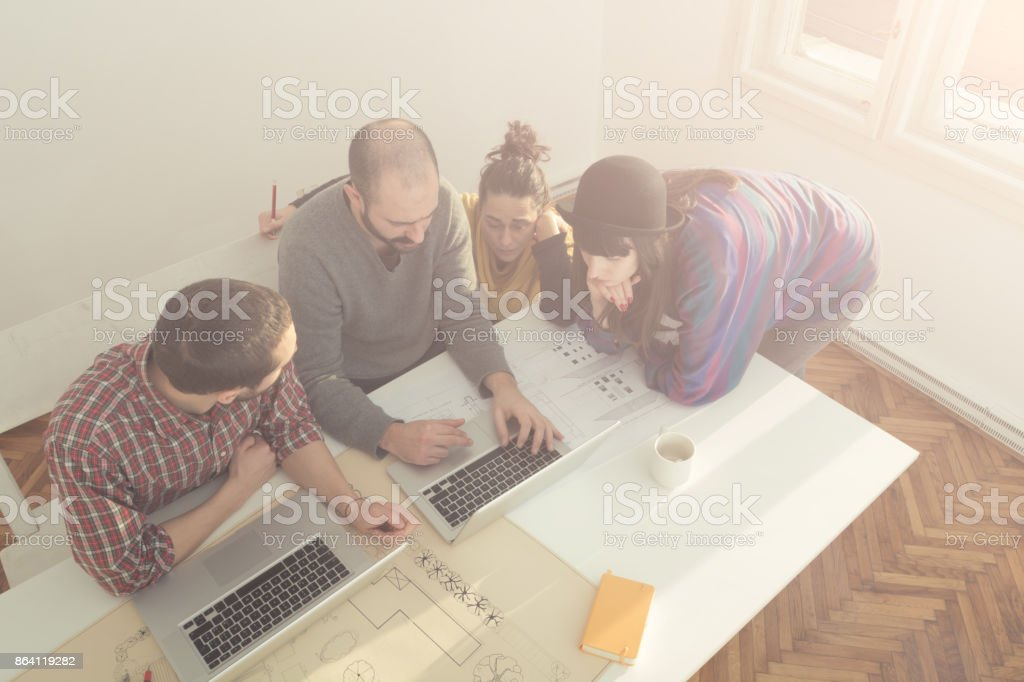 Group of young people / architects being creative in a small office. royalty-free stock photo