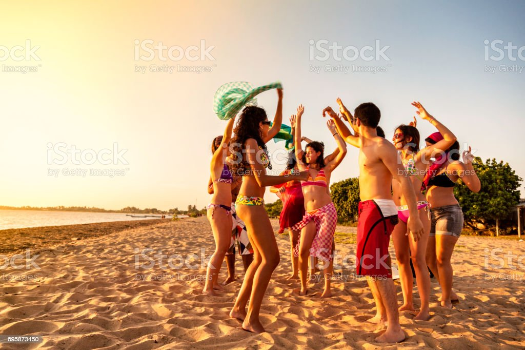 Group of young people at a hot summer tropical beach party at late afternoon stock photo