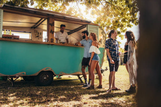 Group of young people at food truck Young people buying street food from a food truck at park. Group of men and woman at food truck. food truck stock pictures, royalty-free photos & images