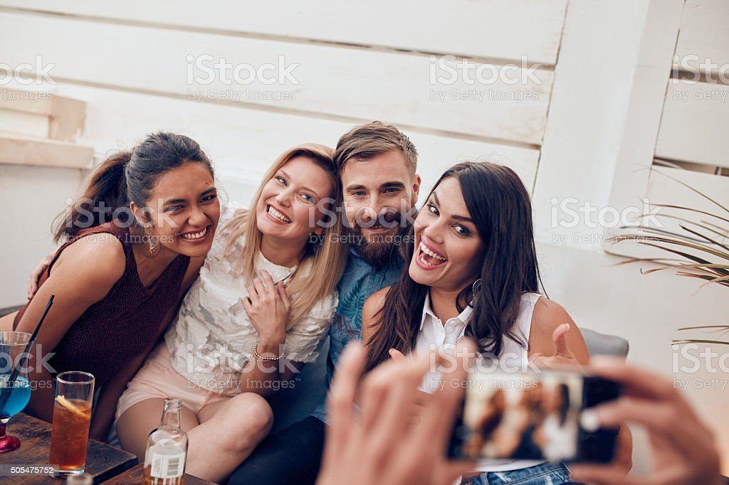 Group of young people at party posing for a photo stock photo