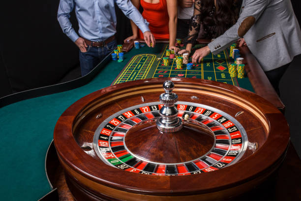 Group of young people behind roulette table stock photo