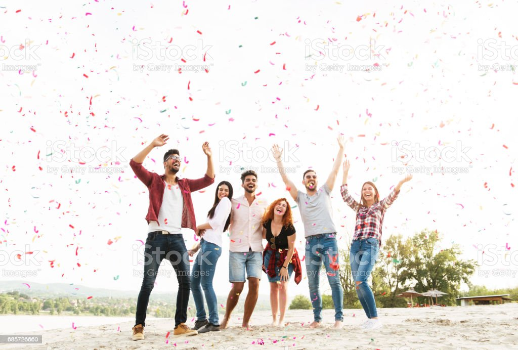 Group of young people celebrating at the beach stock photo