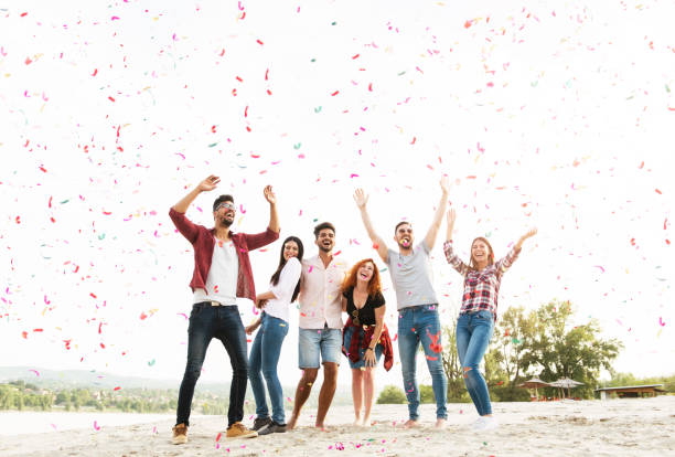 group of young people celebrating at the beach - public celebratory event stock photos and pictures