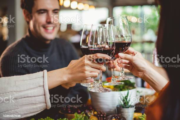 Group Of Young People Celebrating Christmas Party Dinner With Clinking Glass Of Wine - Fotografie stock e altre immagini di Adulto