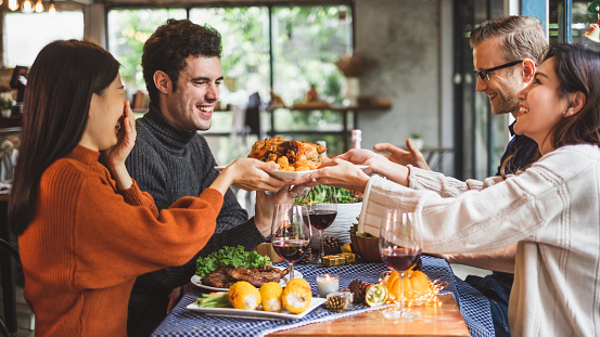 Group of young people celebrating Christmas party dinner with clinking glass of wine