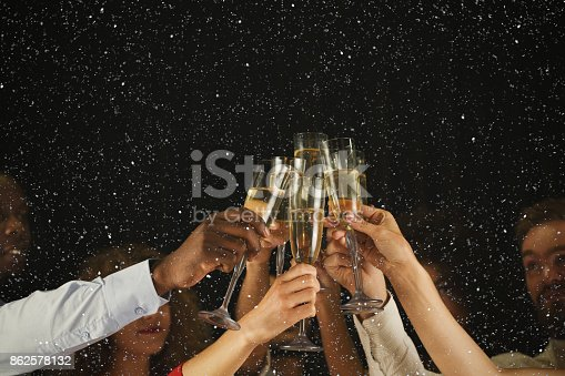 istock Group of young people celebrating new year with champagne at night club 862578132