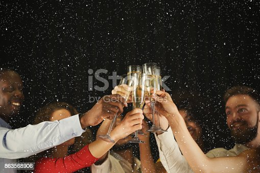 istock Group of young people celebrating new year with champagne at night club 863568906