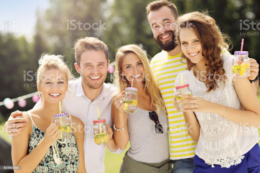 Group of young people cheering and having fun outdoors with drinks stock photo