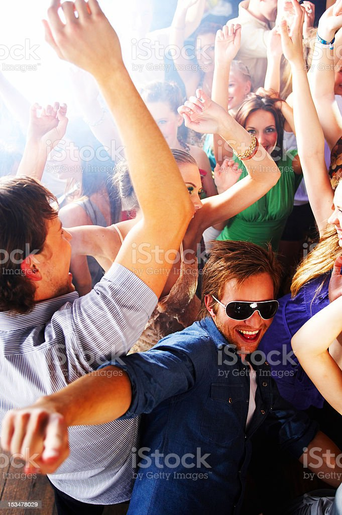 Group of young people dancing at a disco royalty-free stock photo