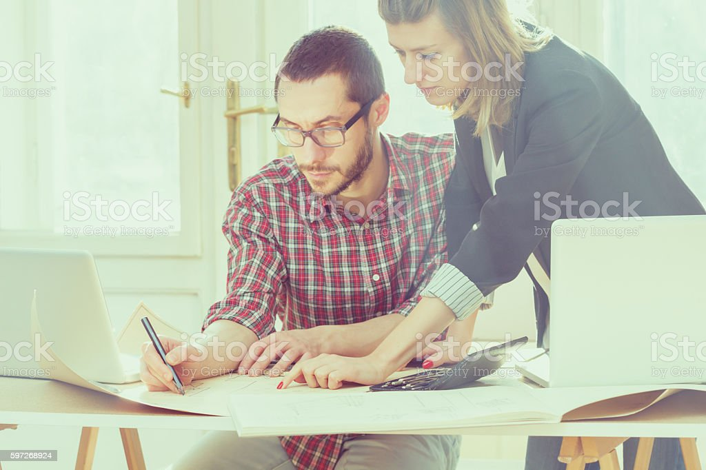 Group of young people discussing business plans, with lap-tops, plans. royalty-free stock photo