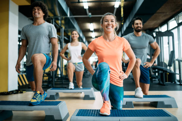 Group of young people doing exercises in gym stock photo