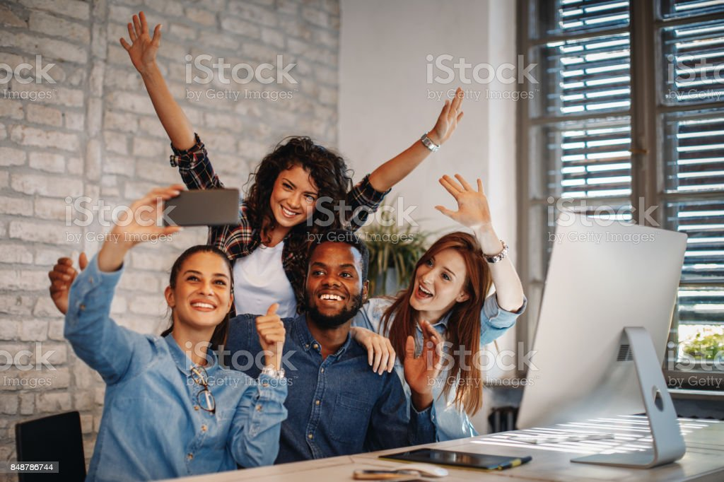 Group of young people doing selfie in the office stock photo