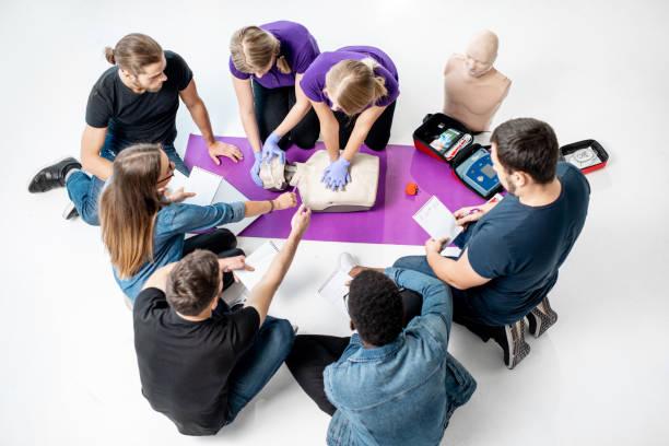 gruppe von jungen menschen während der medizinische erste-hilfe-kurse im haus - wasser sicherheitsausrüstung stock-fotos und bilder