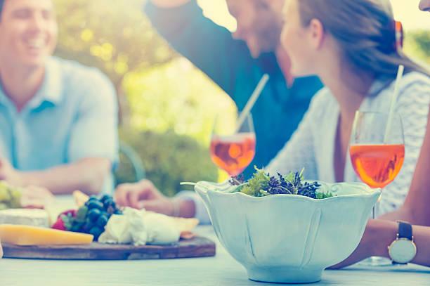 gruppe von jugendlichen essen im freien. - partysalate stock-fotos und bilder