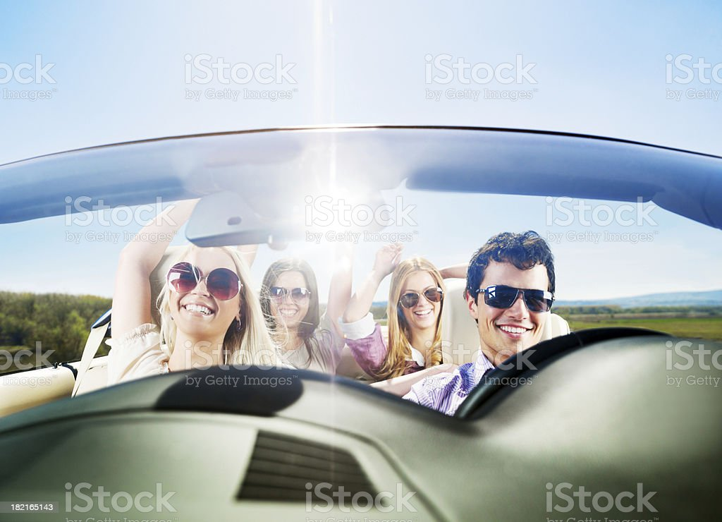 Group of young cheerful people with raised hands are enjoying in the...