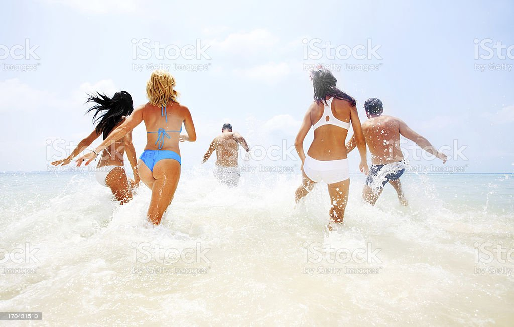 Group of young people entering the water. stock photo