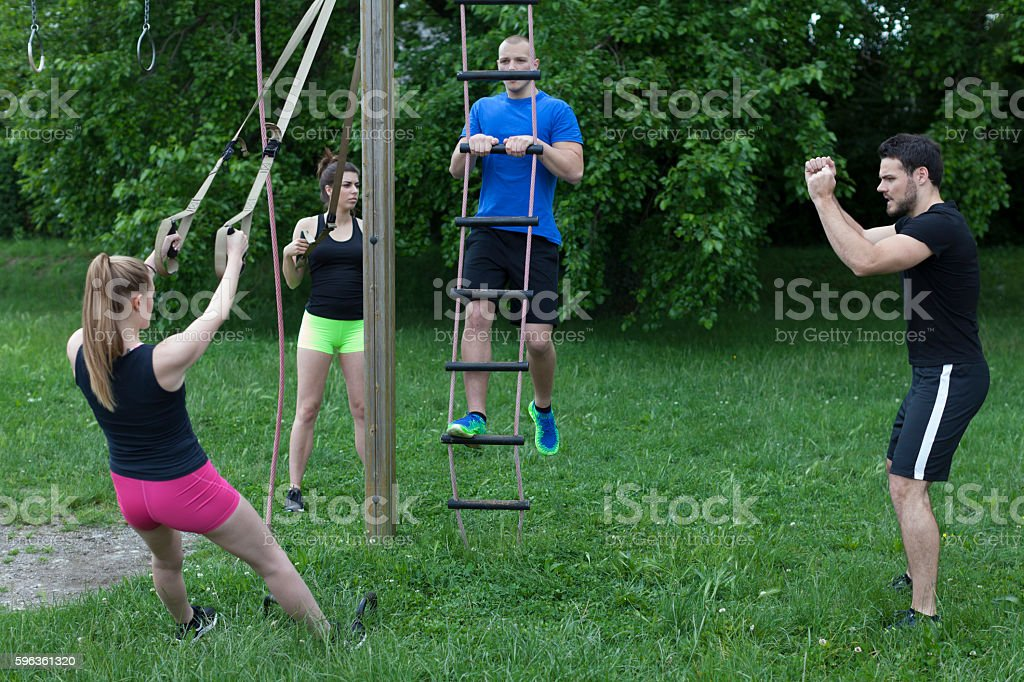 Group of Young People Exercising With a Personal Trainer Outdoors royalty-free stock photo