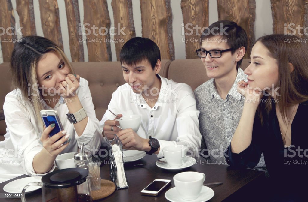 Group of young people from two couples of guys and girls have a tea time in the cafe and looking on the smartphone absorbedly stock photo