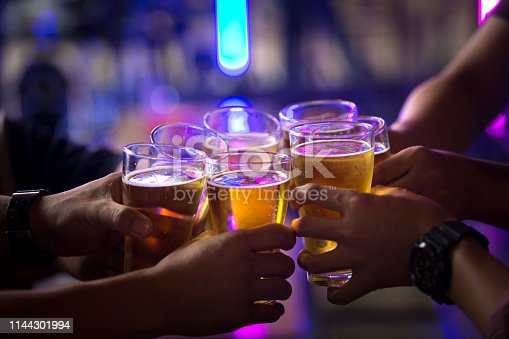 istock Group of  young people hands toasting and cheering aperitif beers half pint 1144301994