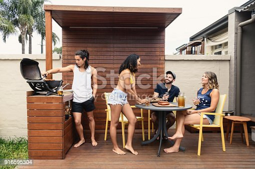 Young men and women talking and relaxing outside, Japanese man cooking on barbecue, three friends at table talking