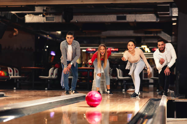 Group of young people having fun in a bowling alley stock photo