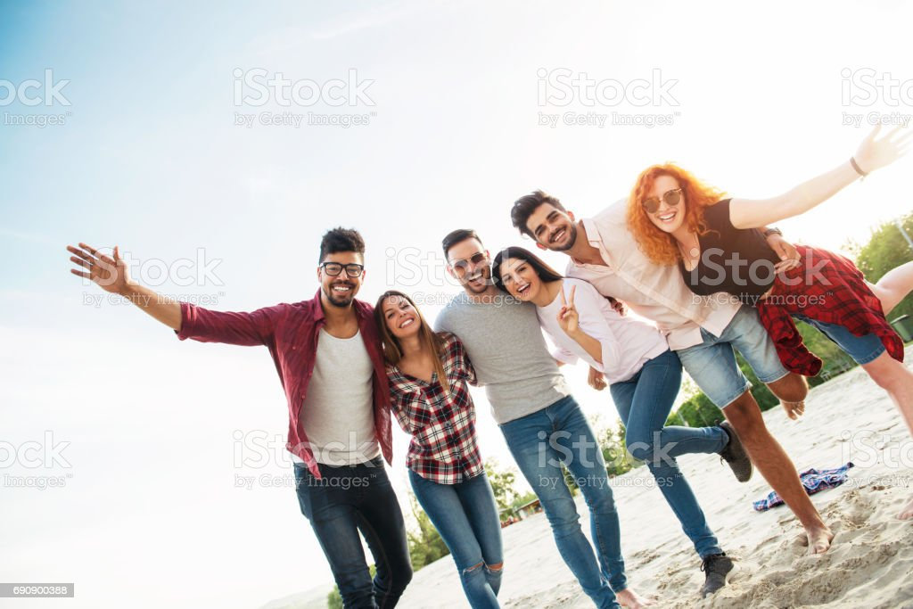 Group of young people having fun outdoors on the beach stock photo