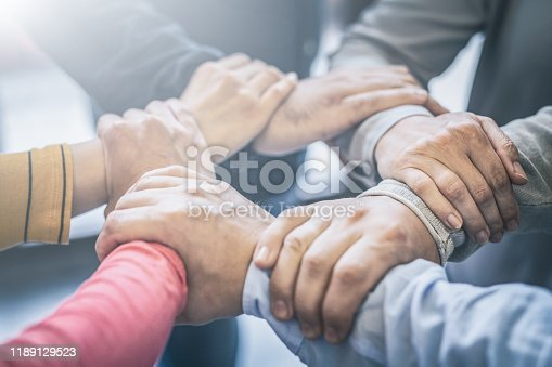 Dramatic moment. A group people hold strong hands. Sign of trust and teamwork. Corporate meeting concept.