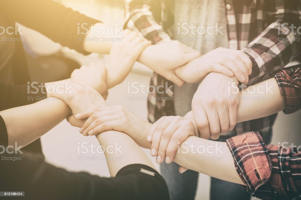 A group of young people hold strong hands. stock photo