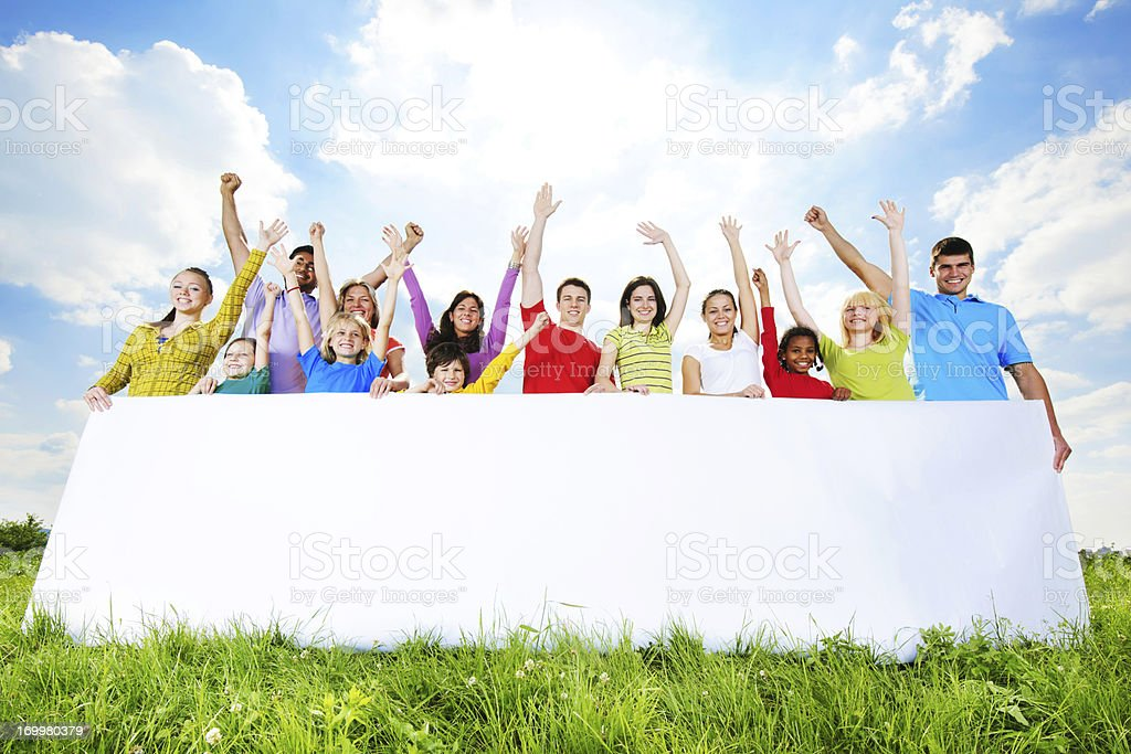 Group of young people holding a white board royalty-free stock photo