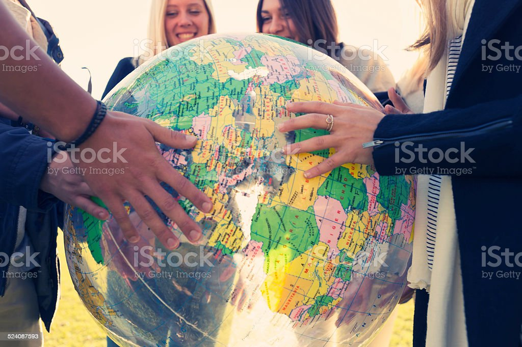 Group of young people holding a world globe stock photo
