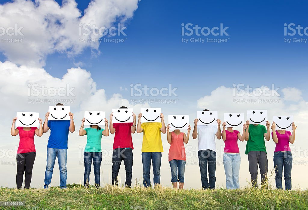 Group of young people holding papers with smileys royalty-free stock photo