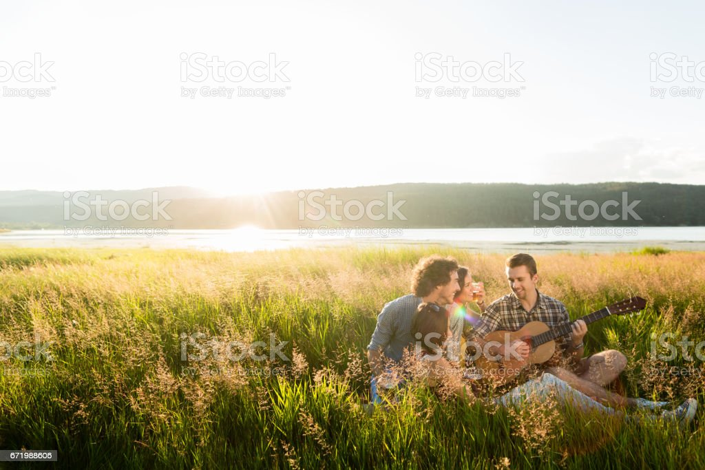 Group of young people in sundown playing guitar music stock photo
