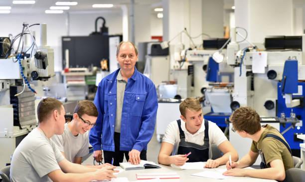 gruppe von jugendlichen in der technischen berufsausbildung mit lehrer - studieren in deutschland stock-fotos und bilder