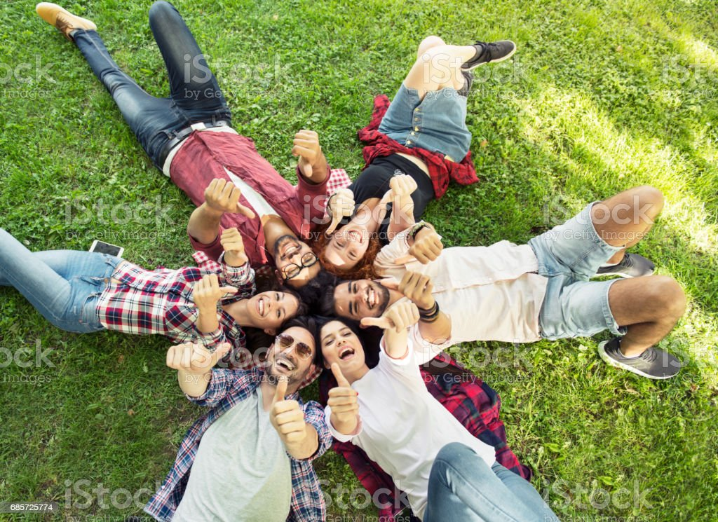 Group of young people laying on the grass in circle, happy, smiling royalty-free 스톡 사진