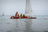 Group of young people learn to drive a boat with a sail. Dinghy Sailing. Outdoor sea sporting activity. Sitges, Catalonia, Spain - May 21, 2017