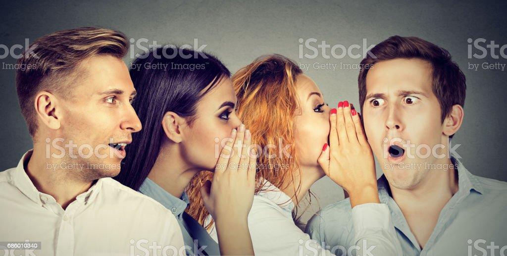 Groupe de jeunes hommes et femmes, l'autre chuchoter à l'oreille - Photo