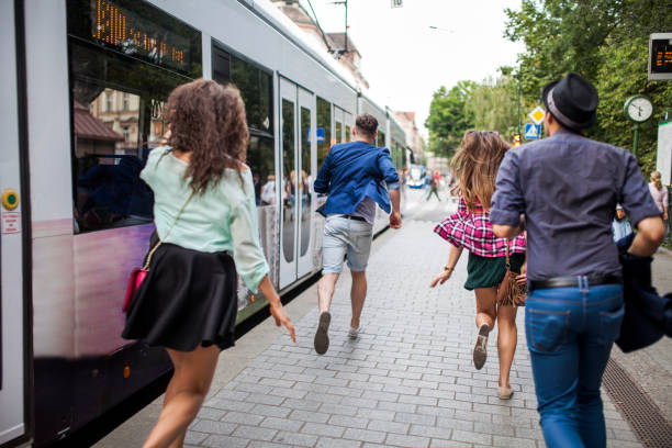 group of young people on a bus/tram stop - urgency stock photos and pictures