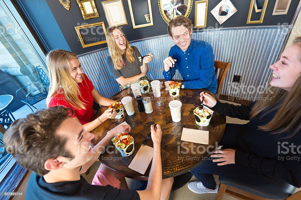 Group of Young People Partying, Socializing in Restaurant stock photo