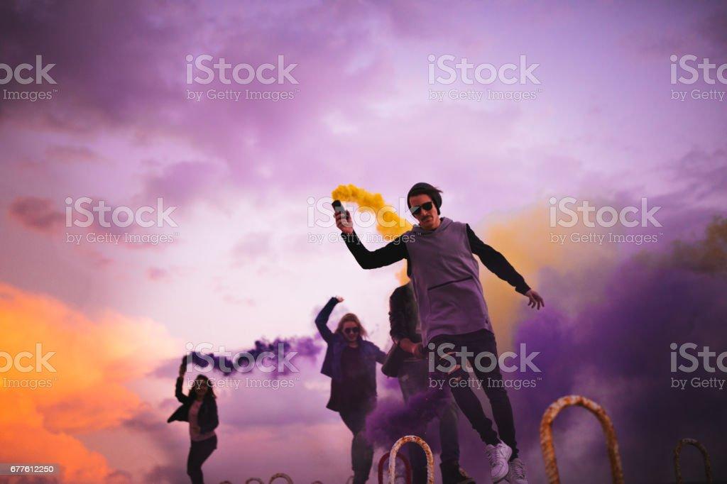 Grupo de jóvenes de fiesta con bombas de humo multicoloras - foto de stock