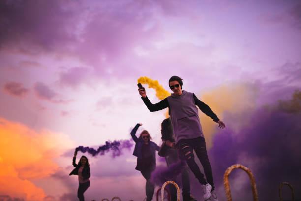 gruppe junger leute, die party mit multi-farbige rauchbomben - lila waffe stock-fotos und bilder