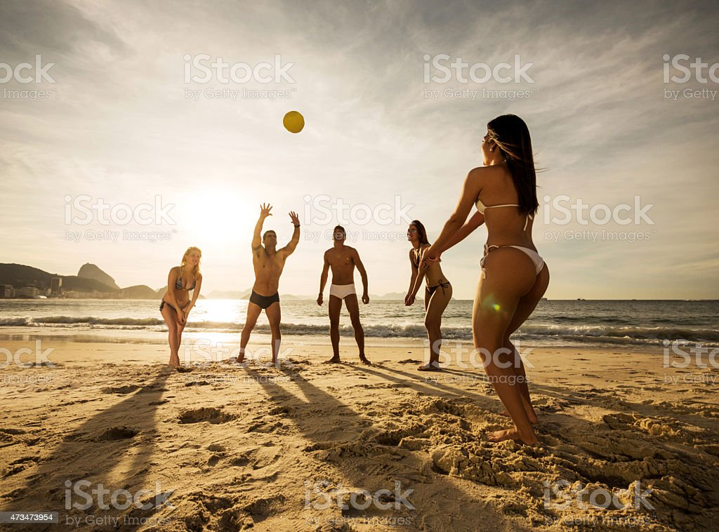 Group of young people playing beach volleyball at sunset.​​​ foto
