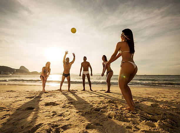 Group of young people playing beach volleyball at sunset. stock photo