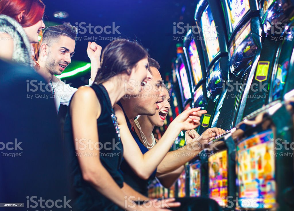 Group of young people playing slot machines at the Casino stock photo