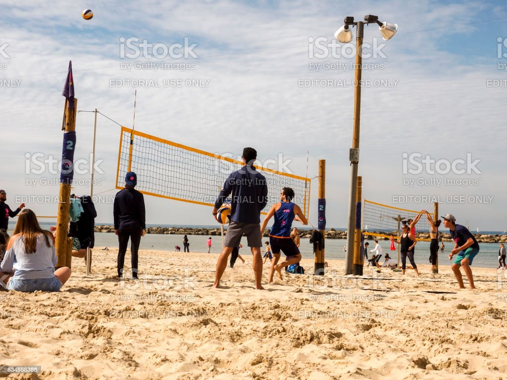Group of young people playing volleyball on the beach of Tel Baruch. Tel Aviv. stock photo