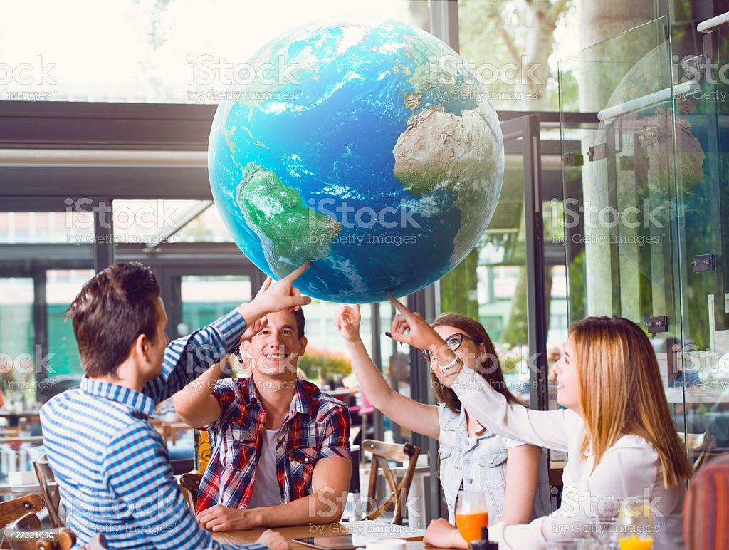 Group of young people pointing at planet Earth Group of young people pointing at planet Earth, sitting at the table 2015 Stock Photo