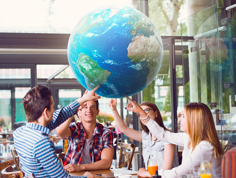 Group Of Young People Pointing At Planet Earth Stock Photo - Download Image Now