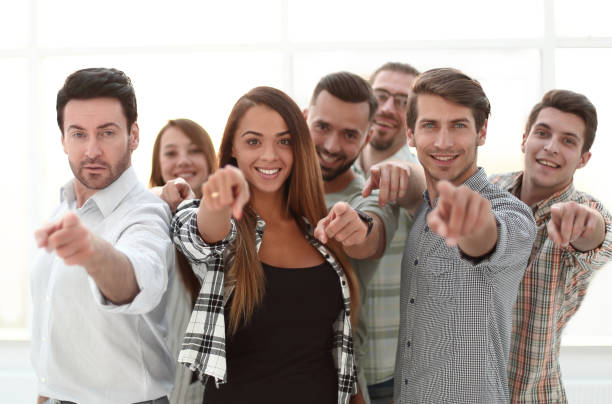 group of young people pointing at you stock photo