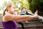 Group of Young People, men and women, Practicing Tai Chi Outdoor, Arms Raised to the sky
