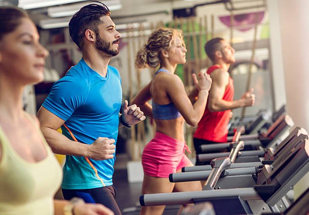 group of young people running on treadmills in a gym. - adults only stock photos and pictures